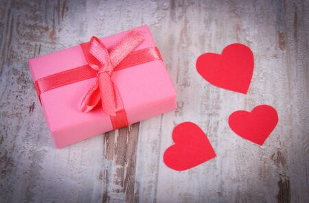 old desk: Wrapped gift for birthday, valentine or other celebration and red heart of paper, symbol of love Stock Photo
