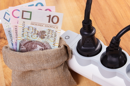 energy costs: Electrical extension with connected plug and polish currency money in jute bag, concept of saving money on electricity, energy costs