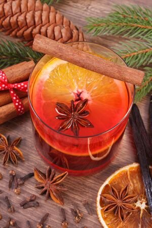 stick of cinnamon: Mulled wine on winter evening on wooden surface plank, spruce branches and spices, cinnamon vanilla anise cloves dried and fresh orange