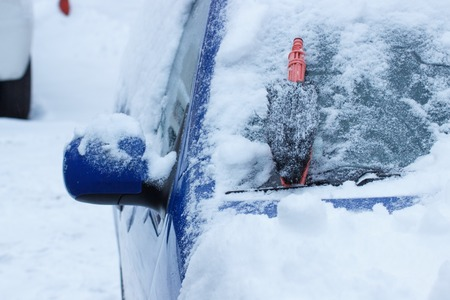 Brush for cleaning car from snow lying on windscreen, concept of transportation and winter