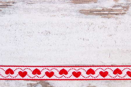 Decorative ribbon with red heart shape on old rustic wooden background, decoration for valentines day, copy space for text