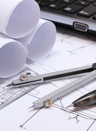 compas de dibujo: Rolls of electrical diagrams, construction drawings of house, accessories for drawing and laptop, drawings and accessories for the projects engineer jobs Foto de archivo