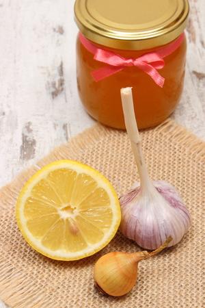 inmunidad: Fresca org�nica cebolla, el ajo, el lim�n y la miel en frasco de vidrio sobre fondo de madera vieja, la nutrici�n saludable, la inmunidad fortalecimiento y tratamiento de la gripe Foto de archivo