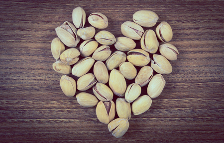 natural love: Vintage photo, Heart shaped roasted pistachio nuts on natural wooden table background, healthy food and nutrition, symbol of love