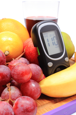 glucometer: Glucometer, fresh ripe natural fruits and glass of juice, concept of healthy eating and diabetes Stock Photo