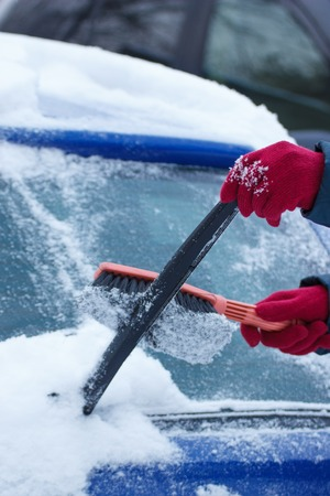 scraping: Hand of woman using brush and remove snow and ice from car and windscreen, concept of transportation and winter