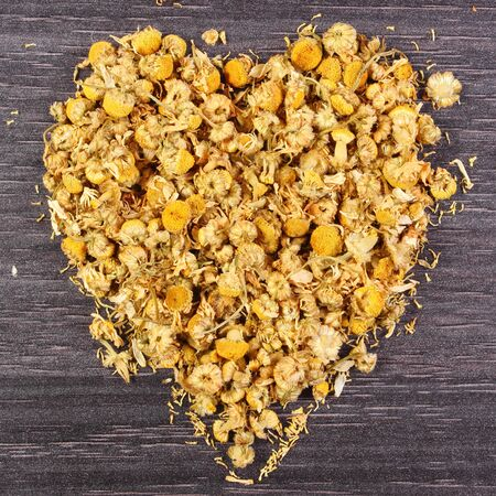 herbalism: Heart shaped dried chamomile on wooden surface, concept of healthy nutrition, herbalism and alternative medicine, symbol of love
