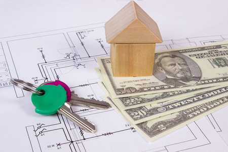 finance concept: House shape made of wooden blocks, home keys and currencies dollar lying on electrical construction drawings of house, concept of building house, drawing for projects