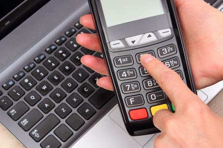 personal identification number: Hand of woman using payment terminal, enter personal identification number, credit card reader and laptop in background, finance and banking concept