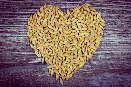 cebada: Foto de la vendimia, toda forma de corazón grano de cebada en el fondo de madera, la nutrición saludable, símbolo del amor Foto de archivo