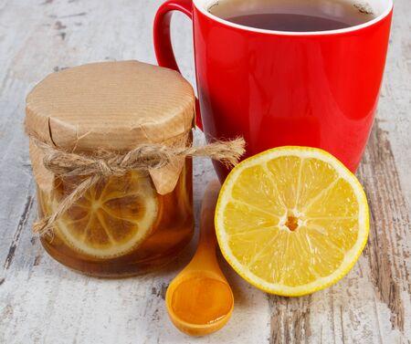 inmunidad: Lim�n con miel en frasco de vidrio, la miel en la cuchara de madera y una taza de t� caliente en la vieja mesa de madera blanca, alimentos saludables, fortalecer la inmunidad y la terapia alternativa