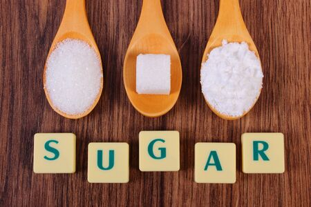 sucrose: Sugar cube, granulated and powdered sugar on wooden spoons with text sugar, ingredient for cooking or baking