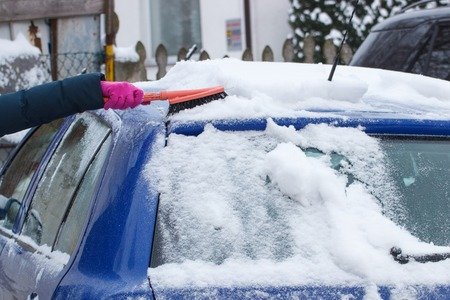 windscreen: Hand of woman using brush and remove snow and ice from car and windscreen, concept of transportation and winter