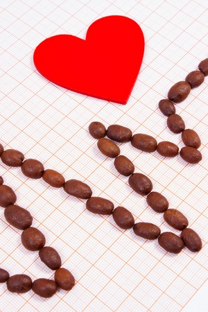 plotting: Electrocardiogram line of brown roasted coffee grains and red heart on graph paper, ecg heart rhythm, medicine and healthcare concept Stock Photo