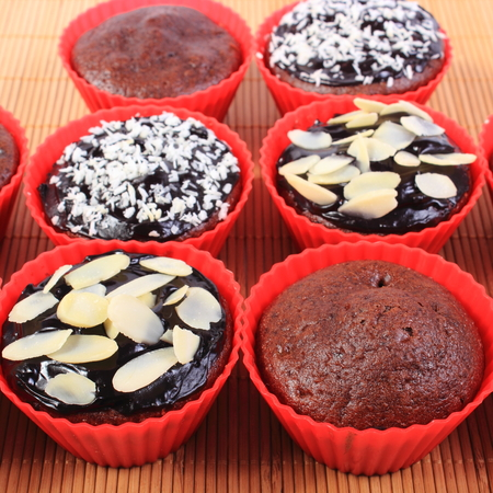 desiccated: Homemade delicious fresh baked chocolate muffins with desiccated coconut and sliced almonds in red silicone cups on wooden background, concept for dessert