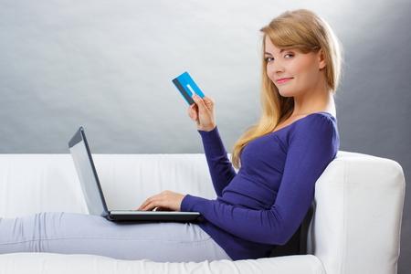 teclado de computadora: Mujer que sostiene la tarjeta de cr�dito usando la computadora port�til sentados en el sof�, el pago a trav�s de Internet para compras en l�nea, escribiendo en el teclado del ordenador, navegar por Internet, la tecnolog�a moderna