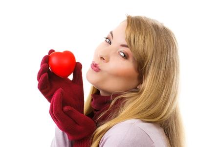 femme romantique: Heureuse femme avec des gants de laine, tenant Valentine coeur rouge et l'envoi baiser