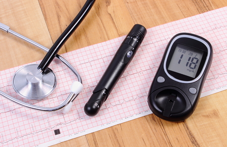 ecg heart: Glucose meter with lancet device and medical stethoscope lying on electrocardiogram graph, ecg heart rhythm Stock Photo