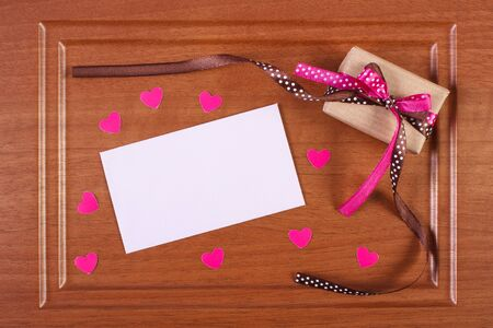 envelope decoration: Wrapped gift with ribbon and love letter in envelope on wooden background, decoration for Valentines Day, copy space for text Stock Photo