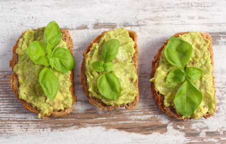 acids: Freshly prepared sandwiches with paste of avocado, rye bread, basil, concept of healthy food, nutrition and omega fatty acids Stock Photo