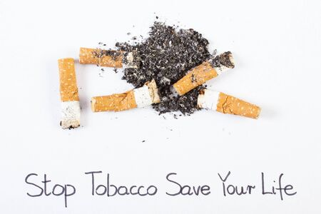 pernicious habit: Cigarette butts and ash with inscription stop tobacco save your life, concept of healthy lifestyles without cigarettes, world no tobacco day Stock Photo