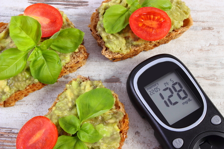 checking ingredients: Glucometer with result of measurement sugar level and freshly sandwiches with paste of avocado, concept of diabetes, healthy food, nutrition and omega fatty acids