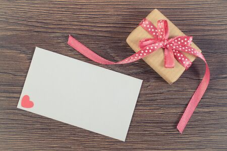 envelope decoration: Vintage photo, Wrapped gift with ribbon and love letter in envelope on wooden background, decoration for Valentines Day, copy space for text