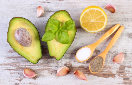 acids: Avocado with ingredients and spices to avocado paste or guacamole, garlic, lemon, basil, concept of healthy food, nutrition and omega fatty acids
