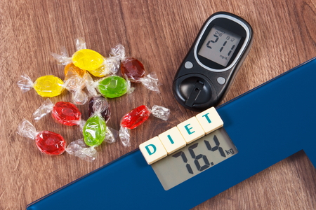 high scale: Electronic bathroom scale and glucose meter with high result of measurement weight and sugar level and heap of colorful candies, diabetes, slimming and reduction eating sweets