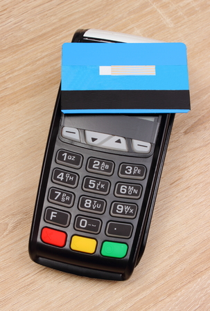 contactless: Payment terminal with contactless credit card on wooden desk, credit card reader, paying using credit card, finance and banking concept Stock Photo