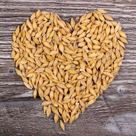cebada: Corazón en forma de grano de cebada entero en el fondo de madera, la nutrición saludable, símbolo del amor