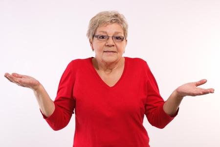 Bejaarde hogere vrouw gooien van haar handen en schouders ophaalt, menselijke emoties en gebaren, die geen idee
