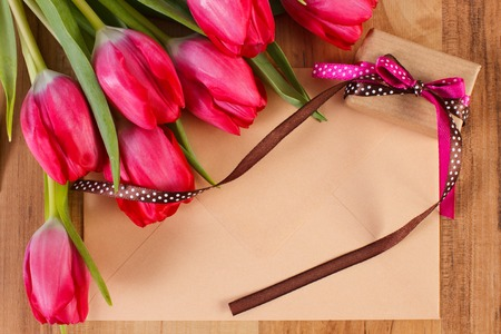 envelope decoration: Bouquet of fresh tulips, love letter in envelope and wrapped gift with ribbon, decoration for Valentines Day Stock Photo