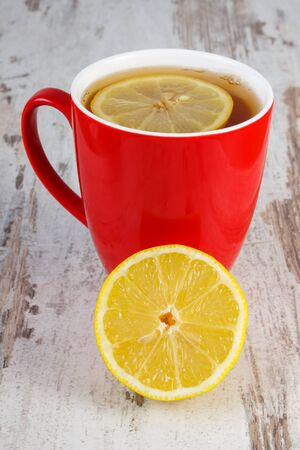 immunity: Fresh lemon and cup of hot tea with lemon on old wooden white table, healthy nutrition, strengthening immunity and alternative therapy