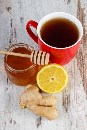 warming therapy: Fresh lemon, honey in glass jar, ginger and cup of hot tea on old wooden white table, healthy food, strengthening immunity and alternative therapy