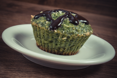 desiccated: Vintage photo, Homemade fresh muffin baked with wholemeal flour with spinach, desiccated coconut and chocolate glaze, delicious, healthy dessert or snack