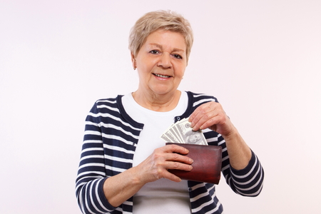 financial security: Happy smiling senior woman, an elderly pensioner holding leather wallet with currencies dollar, concept of financial security in old age