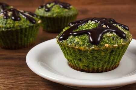 muffin: Homemade fresh muffins baked with wholemeal flour with spinach, desiccated coconut and chocolate glaze, delicious, healthy dessert or snack