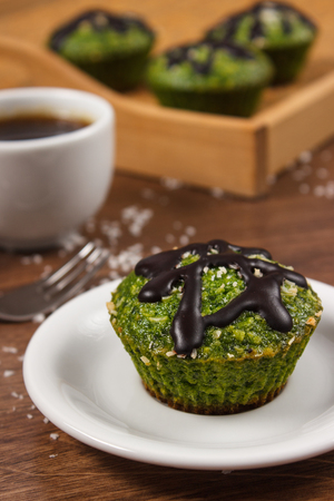 desiccated: Homemade muffins baked with wholemeal flour with spinach, desiccated coconut and chocolate glaze, cup of coffee, delicious, healthy dessert or snack Stock Photo