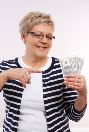 financial security: Happy smiling senior woman, an elderly pensioner showing currencies dollar, concept of financial security in old age