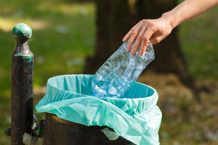 botar basura: Mano de la mujer que lanza la botella de plástico en viejo bote de basura, el concepto de protección del medio ambiente, basura del medio ambiente
