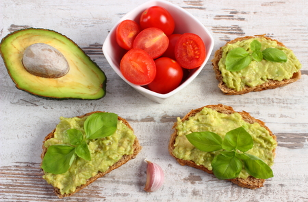 acids: Ingredients and freshly prepared sandwiches with paste of avocado, rye bread, cherry tomatoes, garlic, basil, concept of healthy food, nutrition and omega fatty acids