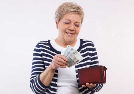 Happy smiling senior woman, an elderly pensioner holding leather wallet with polish currency money, concept of financial security in old age