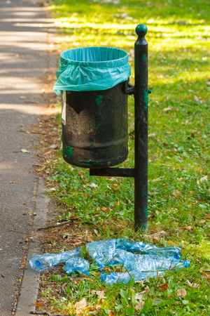public waste: Old trash can in park and heap of plastic bottles, concept of environmental protection, littering of environmental