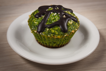 desiccated: Homemade fresh muffin baked with wholemeal flour with spinach, desiccated coconut and chocolate glaze, delicious, healthy dessert or snack