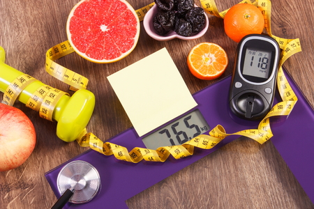 results: Electronic bathroom scale and glucose meter with result of measurement weight and sugar level, concept of healthy lifestyles, diabetes and slimming, sheet of paper for text Stock Photo