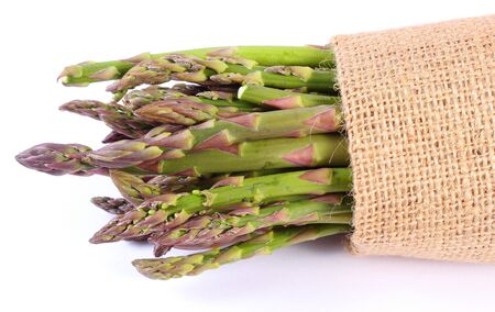 inmunidad: Bunch of fresh green asparagus harvest in burlap bag, concept of healthy food, nutrition and strengthening immunity. White background
