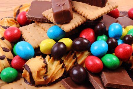 azucar: Mont�n de dulces y galletas en la mesa de madera, demasiados dulces, el concepto de alimentos poco saludables y la reducci�n de comer dulces