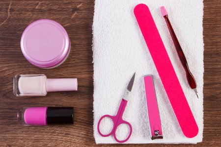 remover: Cosmetics and accessories for manicure or pedicure, nail file, nail polish and remover, scissors, nail clippers, fluffy towel, concept of nail care Stock Photo