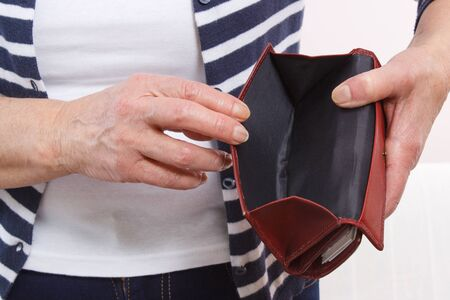 penniless: Hands of elderly woman pensioner holding and showing empty leather wallet, concept of financial security in old age
